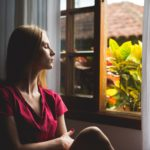 woman sitting by open window with eyes closed