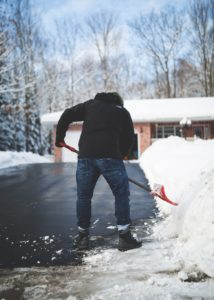 man shoveling snow from driveway in front of house