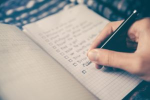 adult writing a checklist in a journal