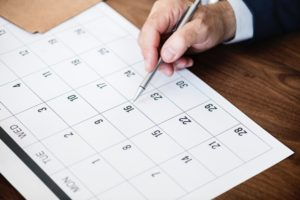 man holding pen over a monthly calendar image
