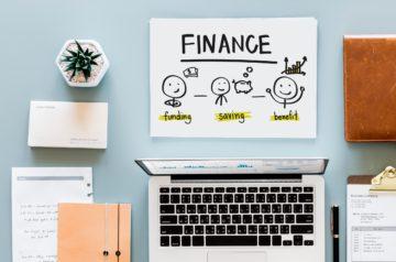 the word finance written on paper beside a laptop computer