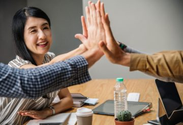 people giving high five around table indicating success