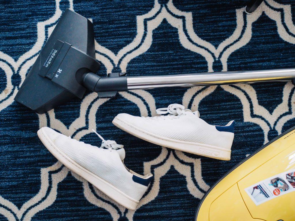 sneakers beside vacuum on carpet